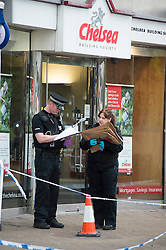 "© London News Pictures. 07/05/2013. Sunbury-On-Thames, UK. Police officers carrying evidence bags outside Chelsea Building Society in Sunbury-on-Thames, in Surrey, which was robbed earlier today (Wed). 55-year-old escaped prisoner Michael Wheatley AKA ""Skull Cracker"", who was arrested in east London, is alleged to have carried out the robbery. Photo credit: Ben Cawthra/LNP"