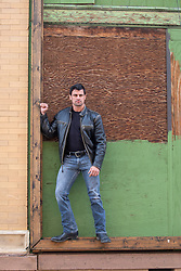 rugged good looking man standing in a boarded up doorway