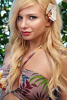 Portrait of young and sensual blonde woman outdoors with a flower
