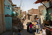 Children head towards a man and his cart as he wonders down the small back streets of Cairo, Egypt, selling prickly pears. Prickly pears are fruits of Opuntia ficus-indica; they're a large, sweet fruit, more commonly known as tunas.