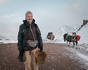 """Paul Salopek on top of the challenging Irshad Pass (4950m), the border between Afghanistan and Pakistan. It snowed for 36 hours straight. Guiding and photographing Paul Salopek while trekking with 2 donkeys across the """"Roof of the World"""", through the Afghan Pamir and Hindukush mountains, into Pakistan and the Karakoram mountains of the Greater Western Himalaya."""
