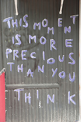 "Sign on a wall ""This Moment Is More Precious Than You Think"""