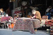 Israel, Jaffa, The flea market. Fixing a Persian carpet