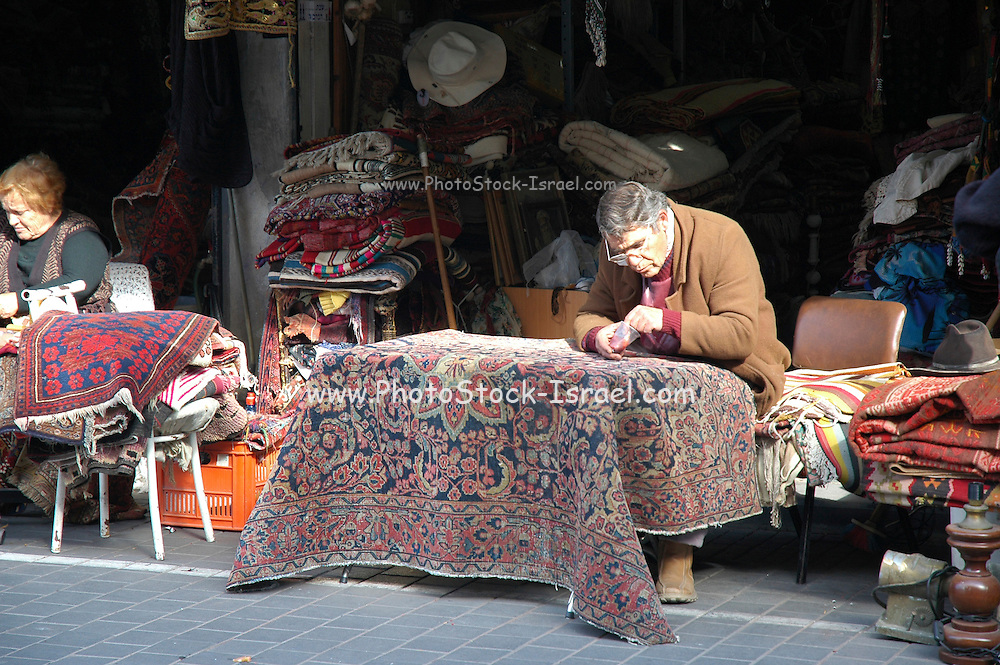 Israel, Jaffa, The flea market. Fixing a Persian carpet