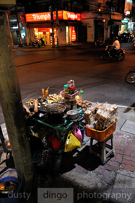 Street vendor cooking and selling a variety of food, including corn, bread buns, sweet potatoes and small shellfish. Vung Tau, Vietnam