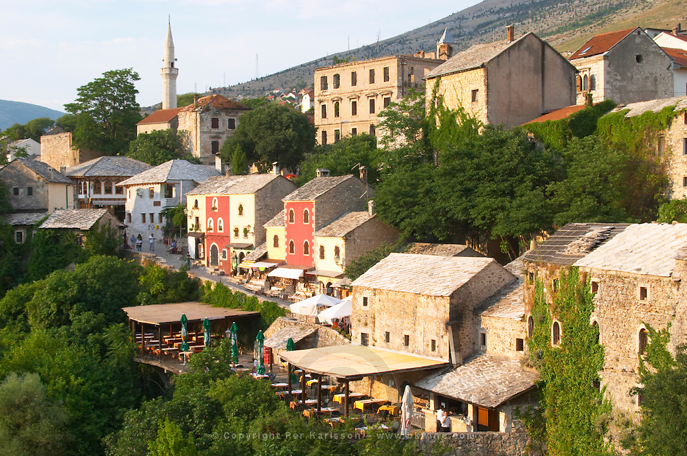 The busy old market bazaar street Kujundziluk with lots of tourist craft and art shops and street merchants. Traditional style houses renovated after the war. Restaurants cafes along the river. Historic town of Mostar. Federation Bosne i Hercegovine. Bosnia Herzegovina, Europe.