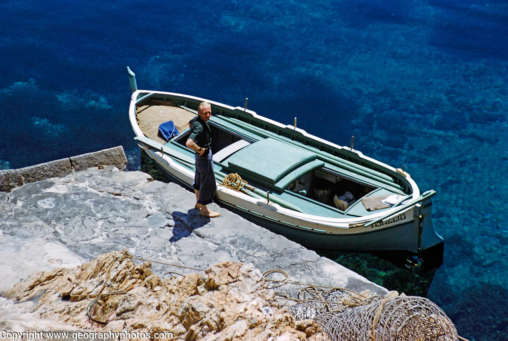 Looking down on small open boat moored on coast of deep blue sea with boatman standing, island of Ibiza, Balearic Islands, Spain, 1950s