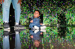 """© Licensed to London News Pictures. 17/05/2021. LONDON, UK. 6 month old Zeki and his father Jay view """"Infinity Mirrored Room – Filled with the Brilliance of Life"""", 2011, by Yayoi Kusama. Preview of Yayoi Kusama: Infinity Mirror Rooms on show at Tate Modern, in partnership with Bank of America with additional support from UNIQLO, from 18 May to 12 June 2022. [Permission granted] Photo credit: Stephen Chung/LNP"""