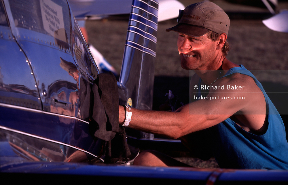 The owner of a home-built aeroplane polishes its shiny surfaces during the world's largest aviation airshow at Oshkosh, Wisconsin, USA, at Oshkosh Air Venture, the world's largest air show in Wisconsin USA. Close to a million populate the mass fly-in over the week, a pilgrimage worshipping all aspects of flight. The event annually generates $85 million in revenue over a 25 mile radius from Oshkosh. The event is presented by the Experimental Aircraft Association (EAA), a national/international organization based in Oshkosh. The airshow is seven days long and typically begins on the last Monday in July. The airport's control tower is the busiest control tower in the world during the gathering.