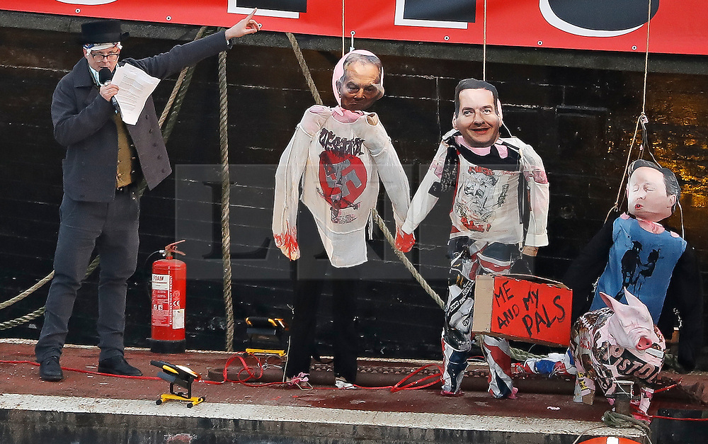 """© Licensed to London News Pictures. 26/11/2016. London, UK. JOE CORRE stands next to effigies of TONY BLAIR, GEORGE OSBORNE and DAVID CAMERON wearing punk memorabilia. Joe Corre, the son of former Sex Pistol manager Malcolm McLaren and Vivienne Westwood burns his personal collection of Sex Pistols punk memorabilia. Earlier this week Joe Corre said that punk has become nothing more than a """"McDonald's brand ... owned by the state, establishment and corporations"""". His collection is estimated to be worth £5 million. Photo credit: Peter Macdiarmid/LNP"""