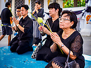"""11 APRIL 2017 - BANGKOK, THAILAND: People pray at Wat Chana Songkhram in Bangkok during a Songkran merit making service. Songkran is the traditional Thai Lunar New Year. It is celebrated, under different names, in Thailand, Myanmar, Laos, Cambodia and some parts of Vietnam and China. In most places the holiday is marked by water throwing and water fights and it is sometimes called the """"water festival."""" This year's Songkran celebration in Thailand will be more subdued than usual because Thais are still mourning the October 2016 death of their revered Late King, Bhumibol Adulyadej. Songkran is officially a three day holiday, April 13-15, but is frequently celebrated for a full week. Thais start traveling back to their home provinces over the weekend; busses and trains going out of town have been packed.     PHOTO BY JACK KURTZ"""