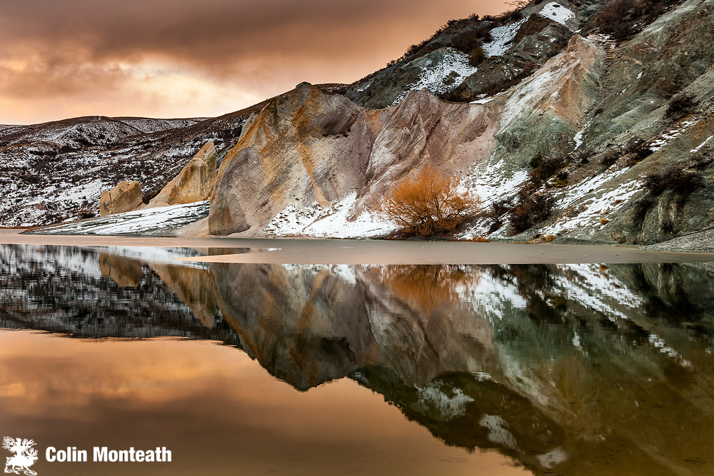 Blue lake reflections of clay cliffs after winter storm and snowfall, St Bathans, Central Otago.
