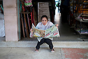 A woman takes a break from work and reads the newspaper, in Fang, Thailand. PHOTO TIAGO MIRANDA