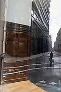 Refected in the window of a closed retailer, a single person walks down Threadneedle Street during the third lockdown of the Coronavirus pandemic, in the 'City of London', the capital's financial district, aka The Square Mile, on 2nd February 2021, in London, England.