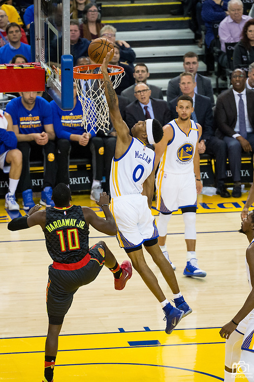 Golden State Warriors guard Patrick McCaw (0) tries to block a lay up by Atlanta Hawks guard Tim Hardaway Jr. (10) at Oracle Arena in Oakland, Calif., on November 28, 2016. (Stan Olszewski/Special to S.F. Examiner)