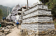 """In the Everest Area of Nepal: Mani stones are stone plates, rocks and/or pebbles inscribed, usually with mantra or ashtamangala, as a form of prayer in Tibetan Buddhism. Out of respect, people should walk to the left or clockwise around Mani Walls. Mani stones are placed in mounds or cairns along roadsides and rivers as an offering to spirits of place (or genius loci). The most common Tibetan prayer is """"Om Mani Padme Hum"""", repeated to invoke compassion. Om Mani Padme Hum means """"Hail to the jewel in the lotus""""."""