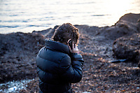 LESVOS, GREECE - FEBRUARY 09: A Syrian refugee tries to call relatives after his arrival to a beach in South Lesvos with other refugees and migrants from the Turkish coast on February 09, 2015 in Lesvos, Greece. Photo: © Omar Havana. All Rights Are Reserved