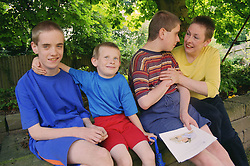 Mother sitting on wall in garden with three sons with autism,