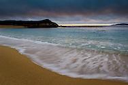 Waves breaking on sand beach at sunset, Carmel River State Beach, California