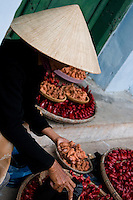 A street vendor wearing a conical hat selling trinkets and souvenirs in the old town of Hoi An, Vietnam.