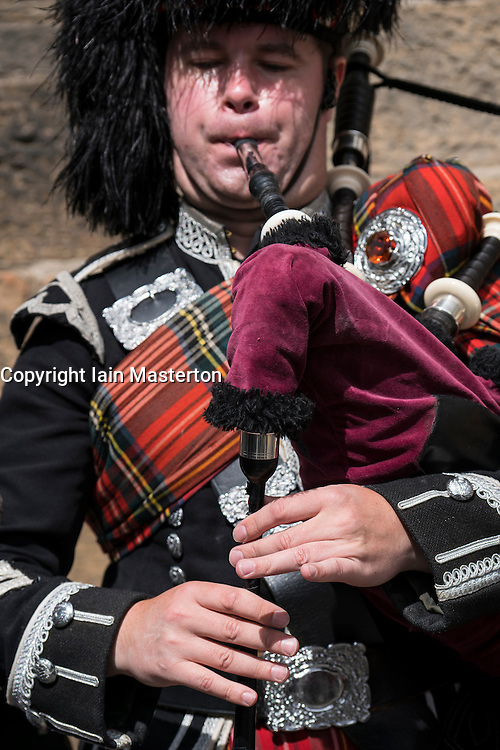Detail of man playing bagpipes for tourists wearing traditional military uniform with tartan and kilt in Edinburgh, Scotland, united Kingdom
