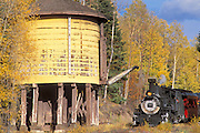 Steam train passing a water tower and fall aspens near Chama, Cumbres and Toltec Scenic Railroad, New Mexico
