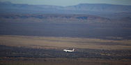An aeroplane carrying FIFO (Fly In Fly Out) workers prepares to land at a mine site against a Pilbara backdrop.