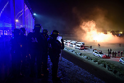© Licensed to London News Pictures. 23/10/2016. Calais, France. French riot police watch over as they clash with migrants on the eve of the demolition of the camp. French authorities have given an eviction order to thousands of refugees and migrants living at the makeshift living area of the French coast. Photo credit: Ben Cawthra/LNP