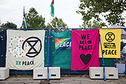 Extinction Rebellion Peace banners are pictured draped over temporary fencing around ExCeL London in advance of the DSEI 2021 arms fair on 12th September 2021 in London, United Kingdom. Activists from a range of different groups continue to protest outside the venue for one of the worlds largest arms fairs.