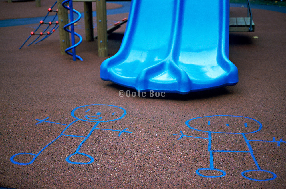 Children's chalk drawings on the side walk in front of a blue slide
