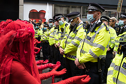 Members of the Extinction Rebellion Red Rebel Brigade line up in front of Metropolitan Police officers during the first day of Impossible Rebellion protests in the Covent Garden area on 23rd August 2021 in London, United Kingdom. Extinction Rebellion are calling on the UK government to cease all new fossil fuel investment with immediate effect. (photo by Mark Kerrison/In Pictures via Getty Images)
