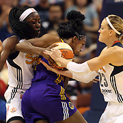 Nneka Ogwumike, Los Angeles Sparks, (wearing face mask), drives between Katie Douglas, (right) and her sisters Chiney Ogwumike, Connecticut Sun, during the Connecticut Sun Vs Los Angeles Sparks WNBA regular season game at Mohegan Sun Arena, Uncasville, Connecticut, USA. 3rd July 2014. Photo Tim Clayton