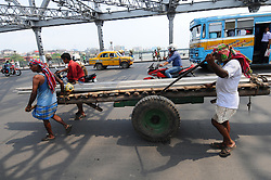June 1, 2017 - Kolkata, West Bengal, India - Indian  labourers pushes a hand cart loaded with Iron material and  cross the howrah bridge in  Kolkata on June 1, 2017.  India's economic growth slowed to 7.1 percent for the 2016-17 financial year,Growth for the 12 months ended March 31 was well below a revised figure of eight percent for the previous year, and follows the government's shock move last November to ban most of the currency in circulation. (Credit Image: © Debajyoti Chakraborty/NurPhoto via ZUMA Press)