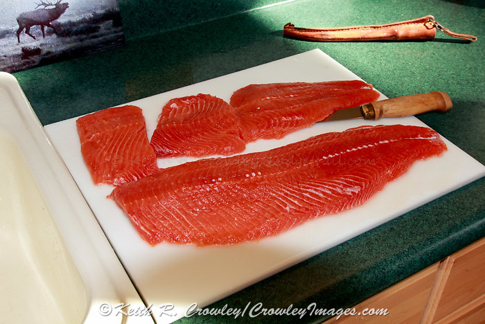 Salmon fillets being prepared on a cutting board.