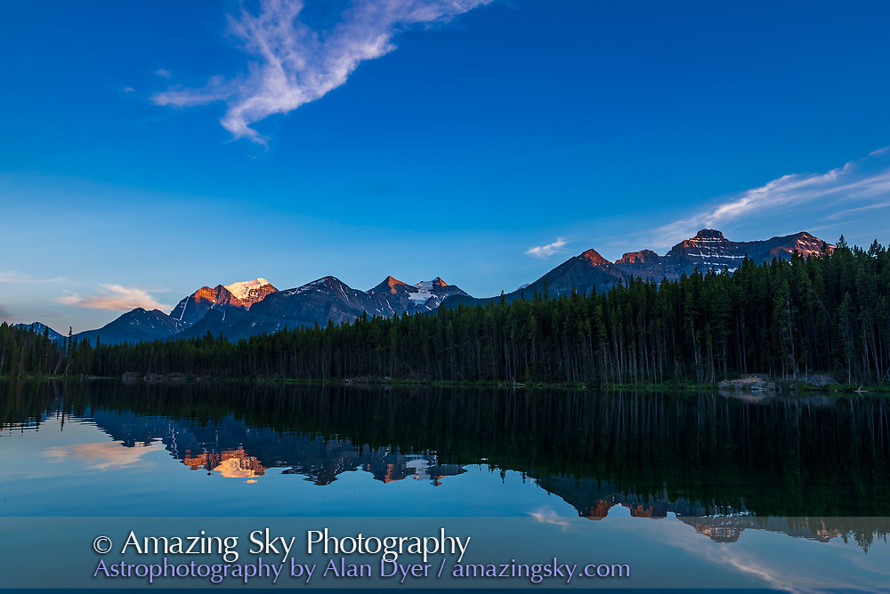 """Sunset at Herbert Lake, Banff National Park, Alberta, with the last sunlight illuminating the peaks around Lake Louise on the Continental Divide, in a show of """"alpenglow."""" The main peak at left is Mount Temple. <br /> <br /> This was July 17, 2018. <br /> <br /> This is a single exposure with the Nikon D750 and Sigma 24mm Art lens."""