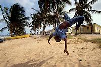 Belice. Placencia.<br /> Un niño hace piruetas en la playa de Seine Bight.<br /> <br /> © JOAN COSTA