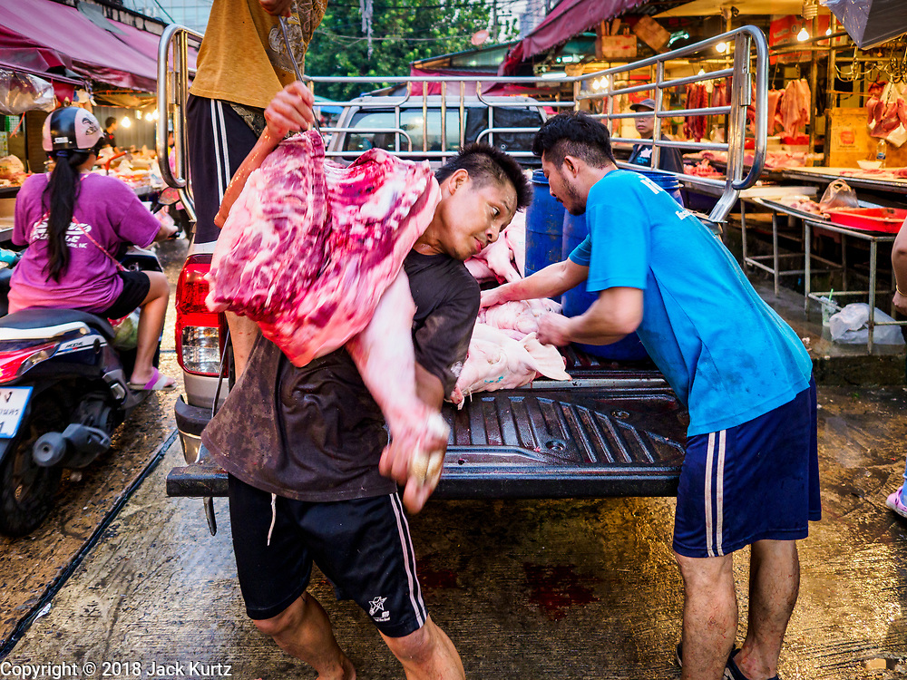 """04 DECEMBER 2018 - BANGKOK, THAILAND:  Butchers deliver sides of pork to venders in Khlong Toei market. Khlong Toey (also called Khlong Toei) Market is one of the largest """"wet markets"""" in Thailand. The market is located in the midst of one of Bangkok's largest slum areas and close to the city's original deep water port. Thousands of people live in the neighboring slum area. Thousands more shop in the sprawling market for fresh fruits and vegetables as well meat, fish and poultry.     PHOTO BY JACK KURTZ"""