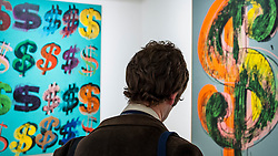 "© Licensed to London News Pictures. 08/06/2015. London, UK. A man stands between (L) at ""Dollar Signs"" and (R) ""Dollar Sign"", both by Andy Warhol, at the preview of ""To the Bearer on Demand"", a private collection of 21 works inspired by the US dollar, including Andy Warhol masterpieces, which will be auctioned on 1 and 2 July.  The collection is estimated to realise £50 million. Photo credit : Stephen Chung/LNP"