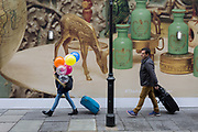 A girl carries balloons beneath the temporary hoardings on the exterior of Harrods in Knightsbridge, on 8th April 2019, in London, England.