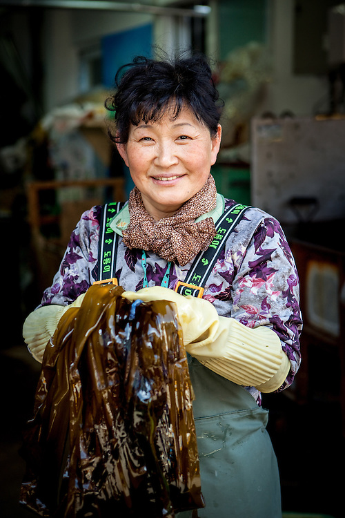 Portrait of a woman holding seaweed in her hands at Jagalchi Fish Market in Busan, South Korea.