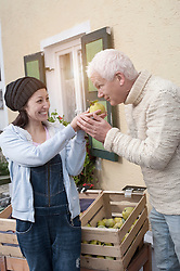 Female shop assistant gives quince to client for smelling, Bavaria, Germany