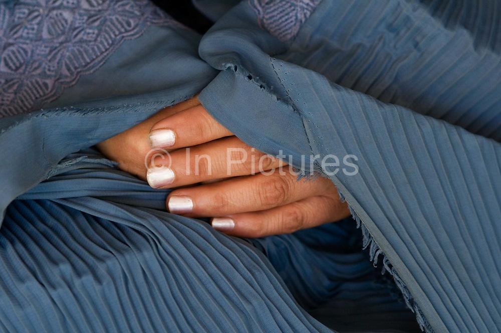 Kabul, Afghanistan. Hands of commercial sex worker Razia, with nail varnish, underneath a burkha.