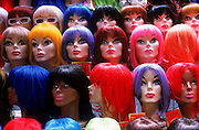A window display of many different colored wigs