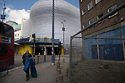 Showing the gap between rich and poor, a homeless man carrying his sleeping bag past the modern landmark architecture of the Selfridges Building in Birmingham, United Kingdom. The building is part of the Bullring Shopping Centre and houses Selfridges Department Store. The building was completed in 2003 at a cost of £60 million and designed by architecture firm Future Systems. It has a steel framework with sprayed concrete facade. Since its construction, the building has become an iconic architectural landmark and seen as a major contribution to the regeneration of Birmingham.