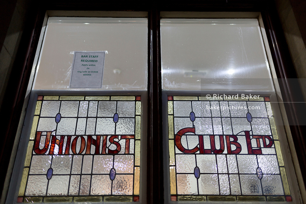 From the outside after dark is the window of the Hexham Conservative & Unionist Club, on 29th September 2017, in Beaumont Street, Hexham, Northumberland, England.