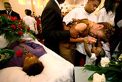 04 August 2006. New Orleans,  Louisiana. .Funeral for victims of Homicide, New Home Baptist Church. Anita Mikell,  victim's aunt is overcome with griefas she is led to the open coffins. A young child reaches up to console her. Friends and relatives of three young men gunned down late at night on a city street on July 28th pay their respects. 4 men were gunned down that night in one incident as crime spirals out of control in New Orleans. Three of the victims, all brothers buried today are Kadeem Stephen (16yrs), Kendall Stephen (21yrs) and Kareem Stephen (also 16yrs). .Photo; Charlie Varley