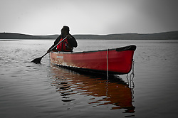 """Sanjayan Muttulingam paddles in the sub arctic waters of the Thelon river August, 2011.  The Thelon is the largest and most remote game sanctuary in North America, which almost no one has heard of.  For the Akaitcho Dene, the Upper Thelon River is """"the place where God began.""""  Sparsely populated, today few make it into the Thelon. Distances are simply too far, modern vehicles too expensive and unreliable. For the Dene youth, faced with the pressures of a western world, the ties that bind the people and their way of life to the land are even more tenuous. Every impending mine, road, and dam construction threatens to sever these connections.(Photo by Ami Vitale)"""