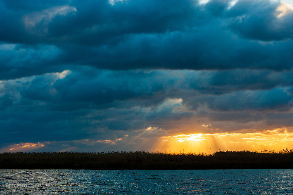 The sun streaks through clearing storm clouds above North Cove in Old Saybrook, Connecticut.  Near the mouth of the Connecticut River.