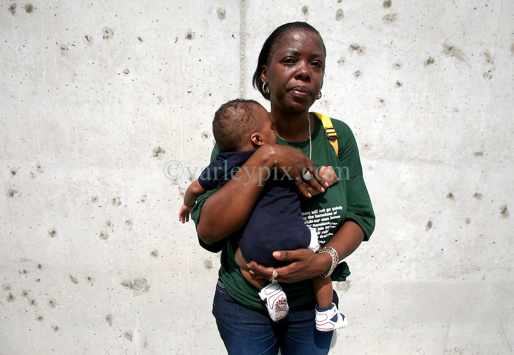 29 August 2006. New Orleans, Louisiana. Lower 9th ward.  <br /> Chevelle Washington (who lost her uncle) and her grandson David (5mts) stands crying beside the newly renovated industrial canal levee flood wall. Civilians gathered at the site of the breach of the industrial canal for the Great Flood commemoration and memorial ceremony to 'honor and remember our loved ones who have passed.' People came to mark the anniversary of devastating hurricane Katrina at the site where the now repaired and allegedly in theory stronger levee flood wall. The levee breached along the industrial canal at the point where people gathered, needlessly killing hundreds of innocent civilians in the worst engineering disaster in US history.