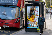 Shoppers walk past an NHS (National Health Service) bus shelter ad on the King's Road during the second lockdown of the UK's Coronavirus pandemic, when all but essential retailers and businesses remain shut according to the government's restriction rules, on 13th November 2020, in London, England.